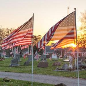 American flags in the Aurora Cemetery during a sunset.