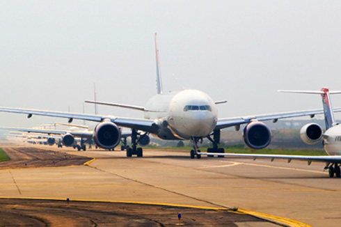 A row of large commercial airplanes on the runway